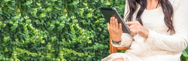 Mujer asiática con sitio web en línea de compras de tableta inteligente en smartphone con cara sonriente.