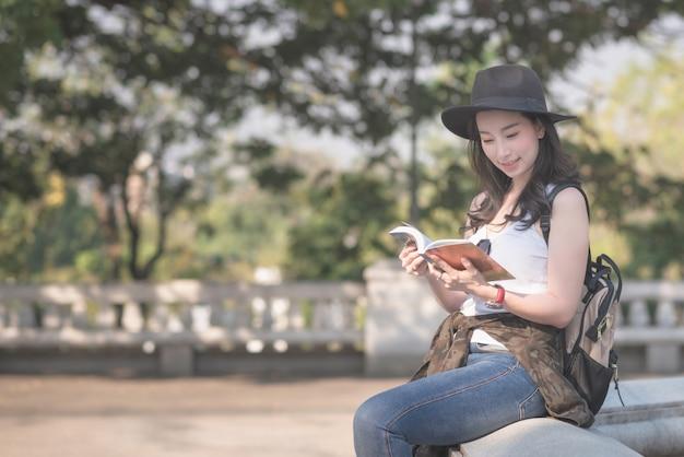 Mujer asiática solista hermosa que lee el libro de guía del viaje que busca para el punto de turismo de los turistas