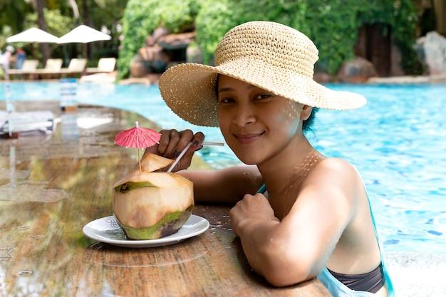 Mujer asiática con sombrero con bebida de coco en la piscina