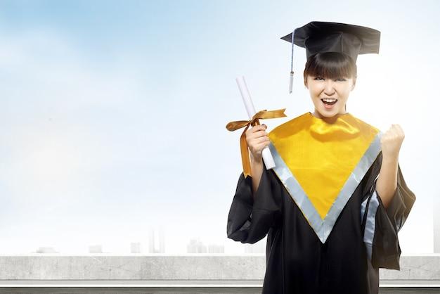 Mujer asiática en sombrero de birrete y diploma de graduarse de la universidad