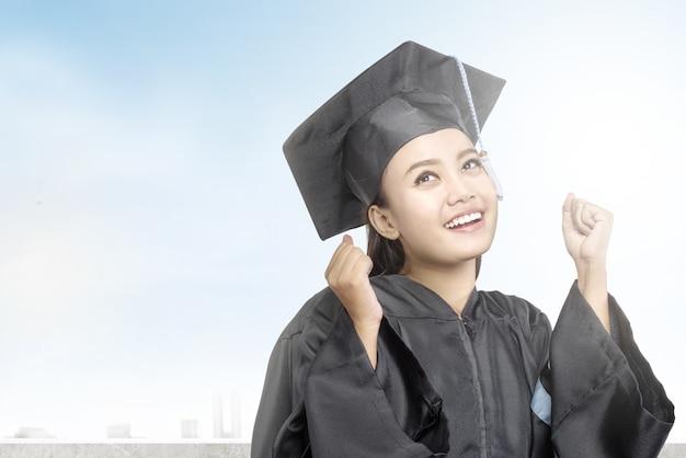 Mujer asiática en sombrero de birrete graduarse de la universidad