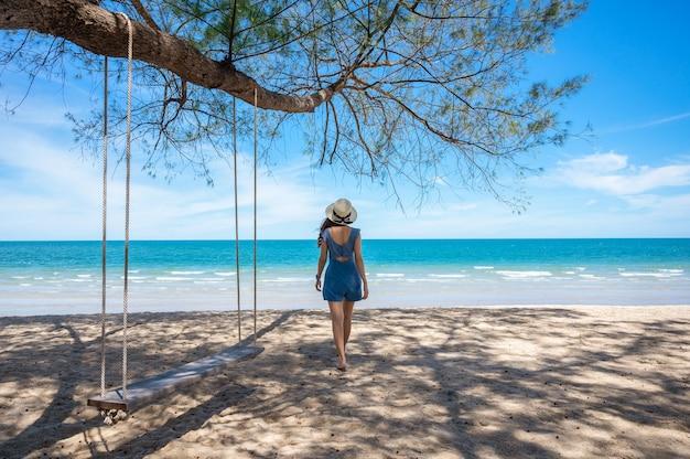 Mujer asiática con sombrero caminando por la playa y columpio de madera colgando de un árbol en el mar tropical