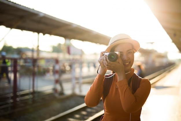 La mujer asiática sonríe con la cámara y toma una foto en la estación de tren.