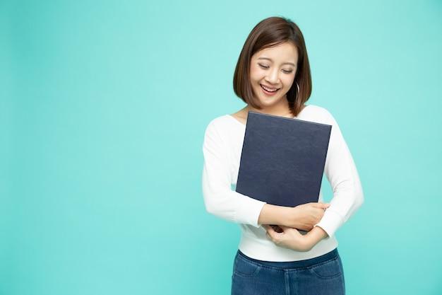 Mujer asiática sonríe y sostiene archivo de documento aislado