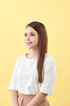 Mujer asiática sonriendo con hoyuelos de pelo largo ojos negros sobre fondo amarillo
