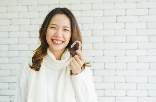 Mujer asiática sonriendo con la mano que sostiene el retenedor de alineador dental (invisible)
