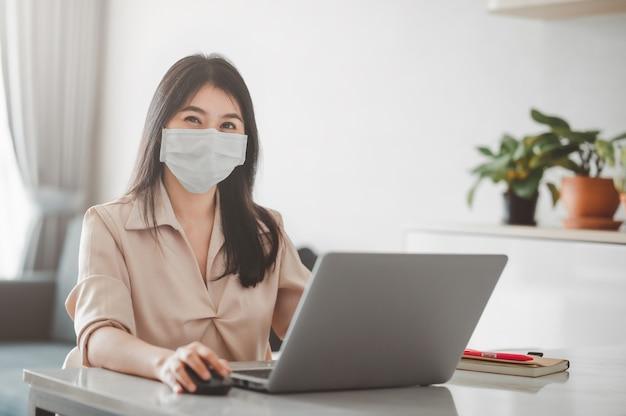 Mujer asiática sonriendo mientras usa mascarilla trabajando en casa con computadora portátil durante la cuarentena por coronavirus