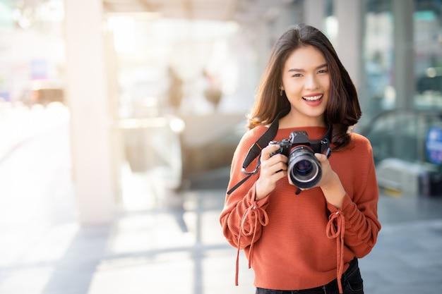 Mujer asiática sonriendo y tomando fotos