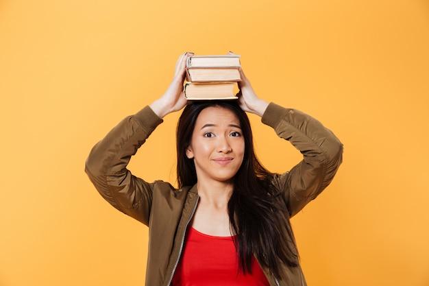 Mujer asiática sonriente en la chaqueta que sostiene los libros en la cabeza