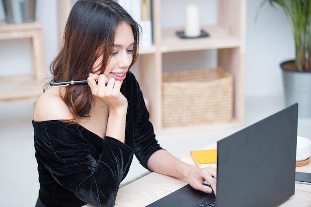 Mujer asiática sonriente hermosa del estudiante que aprende del servicio de educación en línea, mujer asiática joven que hace la tarea con el ordenador portátil, el cuaderno y el teléfono elegante de la computadora