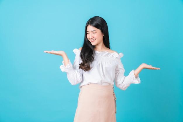 La mujer asiática sonriente joven se coloca y que mira a mano con las palmas abiertas en fondo azul.