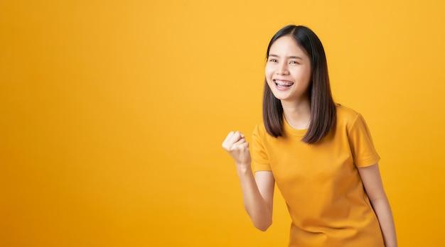 La mujer asiática sonriente de los jóvenes se coloca con asombrado para el éxito y la mirada para copiar el espacio en fondo amarillo.