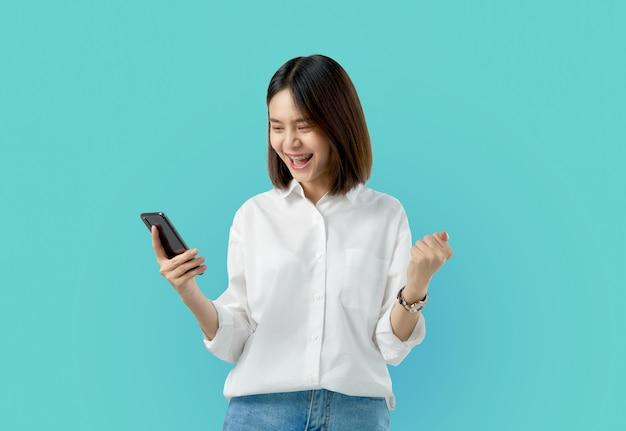 Mujer asiática sonriente de los jóvenes que sostiene el teléfono elegante con la mano del puño y emocionada para el éxito en azul claro