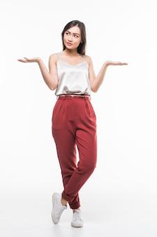 Mujer asiática sonriente con las palmas abiertas que muestran el espacio de la copia para el producto aislado en la pared blanca.