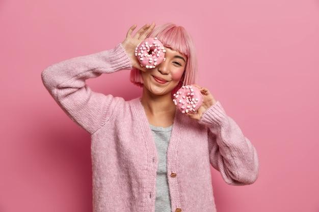 La mujer asiática sonriente positiva se divierte y sostiene dos deliciosas donas, juega con productos azucarados, disfruta de un apetitoso postre, viste un jersey informal,