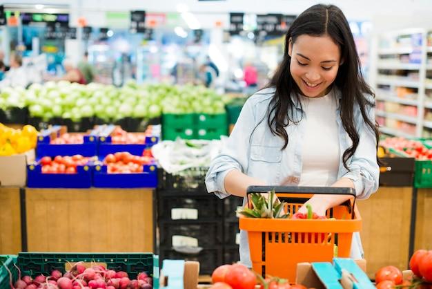 Mujer asiática sonriente que clasifica mercancías en mercado