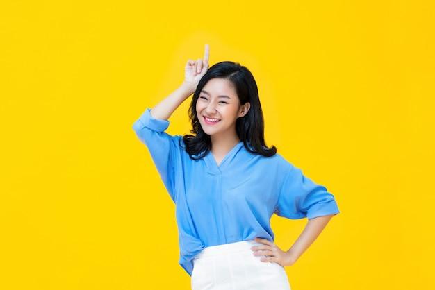 Mujer asiática sonriente que se coloca en estudio