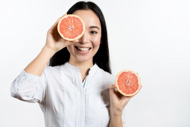 Mujer asiática sonriente que hace la cara divertida sobre el fondo blanco