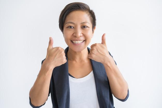 Mujer asiática sonriente que muestra ambos pulgares para arriba