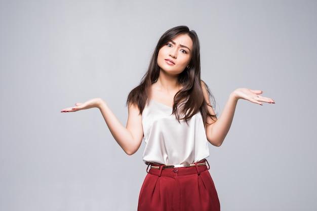 Mujer asiática sonriente que muestra el espacio de la copia para el producto aislado en la pared blanca.