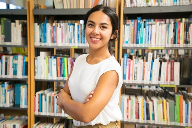 Mujer asiática sonriente que presenta en la biblioteca pública
