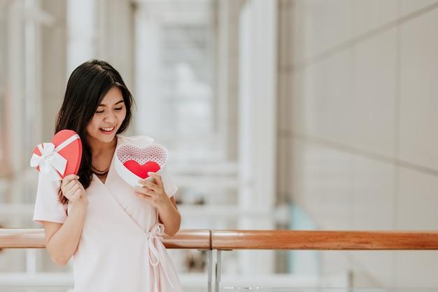 Mujer asiática sonriente que sostiene la caja de regalo con el corazón rojo el día de san valentín