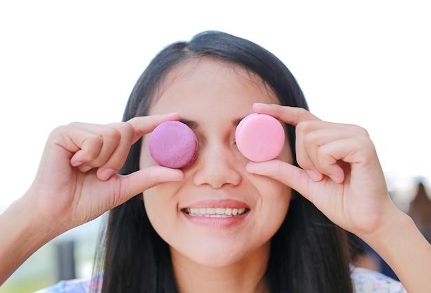 Mujer asiática sonriente que sostiene los macarrones en sus ojos.