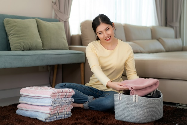 Mujer asiática sonriente que sostiene la ropa doblada limpia en casa. señora bastante joven sentada en el piso con sofá. concepto de lavandería y hogar. vista frontal.