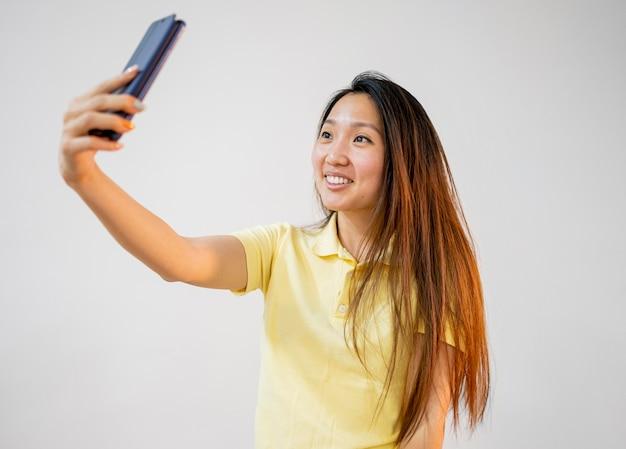 Mujer asiática sonriente tomando un selfie