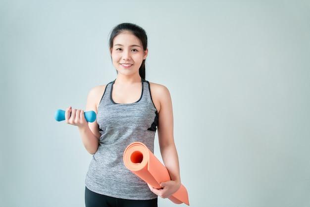 Mujer asiática sonriente vistiendo ropa deportiva con estera naranja con mancuernas azul en la sala de estar. concepto de estilo de vida saludable.