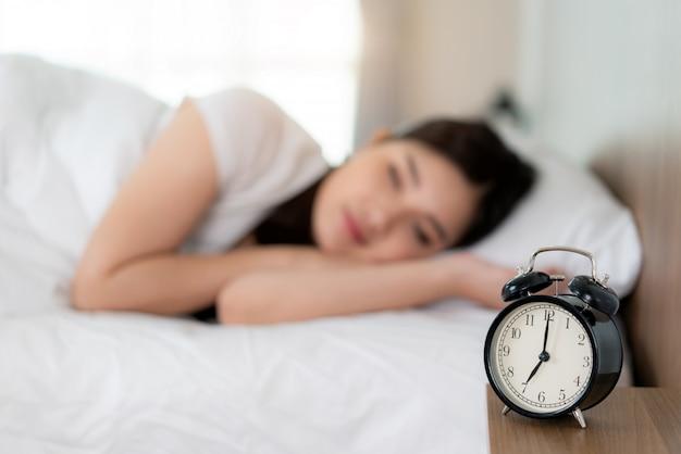 La mujer asiática con sonrisa atractiva disfruta del colchón de lino fresco y suave de la ropa de cama.