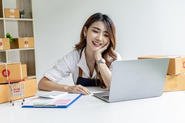 Una mujer asiática con una sonrisa feliz en su rostro después de cerrar los objetivos de ventas, es dueña de una tienda en línea, empaca y envía a través de una empresa de transporte privada. conceptos de venta y compra en línea