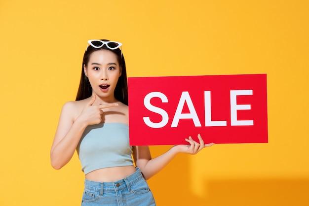 Mujer asiática sorprendida apuntando al cartel de venta rojo en la mano