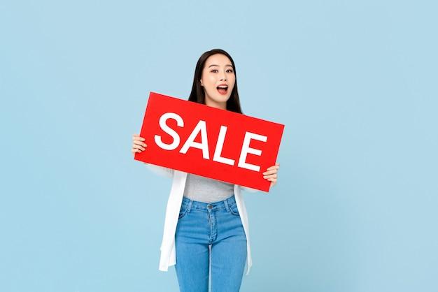 Mujer asiática sorprendida con cartel de venta rojo aislado en pared azul claro
