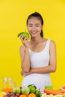 Mujer asiática sostenga las naranjas con la mano derecha, y en la mesa hay muchas frutas.