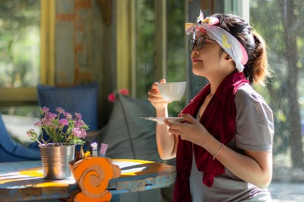 Mujer asiática sosteniendo y bebiendo una taza de café