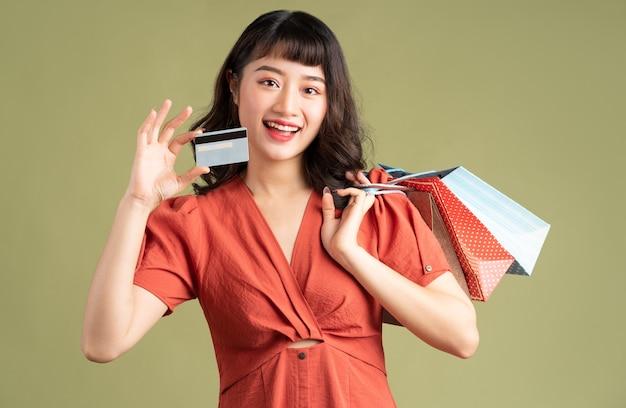 Mujer asiática sosteniendo una bolsa de compras y sosteniendo una tarjeta bancaria