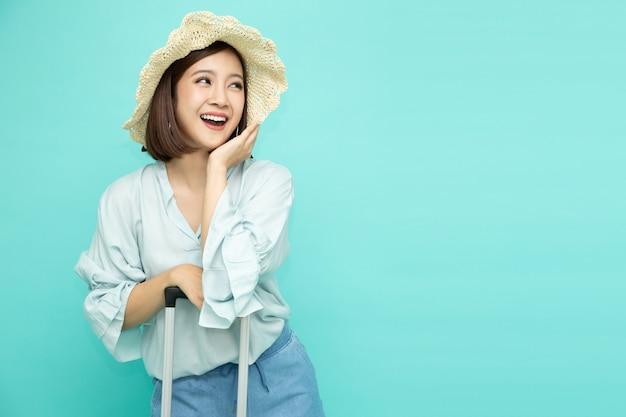 Mujer asiática sosteniendo la maleta y sonriendo aislado