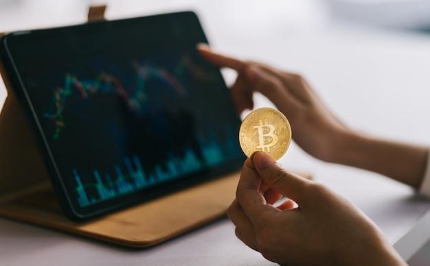 Mujer asiática sosteniendo una moneda en la mano mientras ve el gráfico de cotizaciones