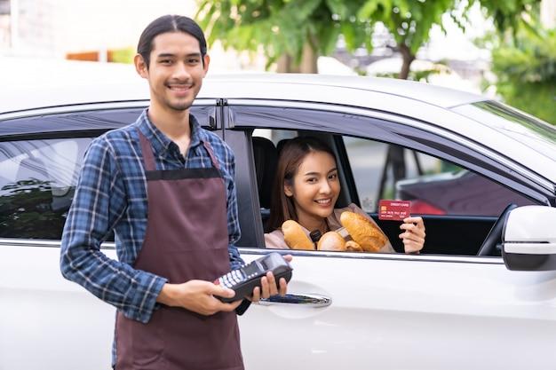 Mujer asiática sosteniendo una tarjeta de crédito y pagando desde el coche