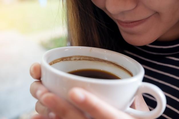 Una mujer asiática sosteniendo una taza de café antes de beber con sentirse bien