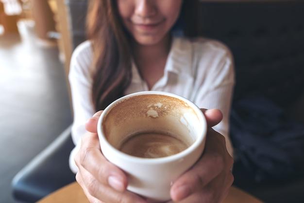 Una mujer asiática sosteniendo una taza de café y bebiendo