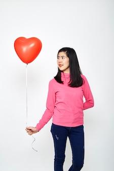 Mujer asiática sosteniendo un globo corazón rojo