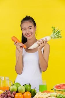Mujer asiática sosteniendo una zanahoria con la mano derecha sostenga el rábano con la mano izquierda y sobre la mesa hay muchas frutas.