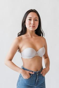 Mujer asiática en sujetador con las manos en los bolsillos.