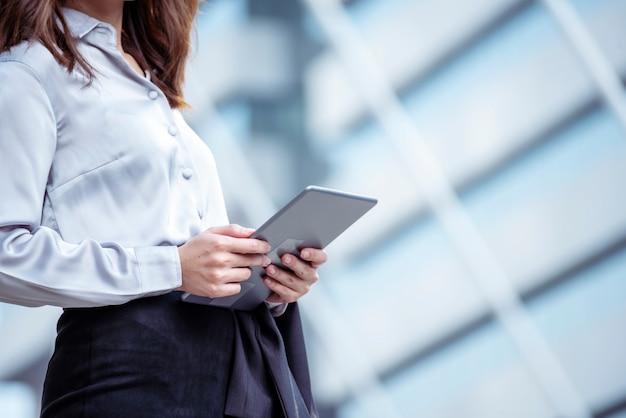 Mujer asiática con tableta en el sitio web de compras en línea en el teléfono inteligente con cara sonriente.