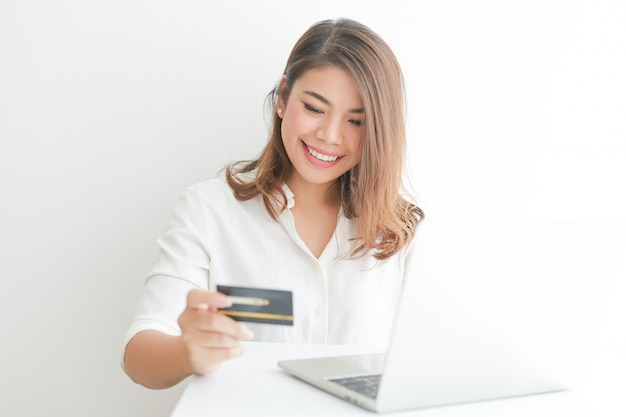 Mujer asiática con tarjeta de crédito de compras en línea con computadora portátil