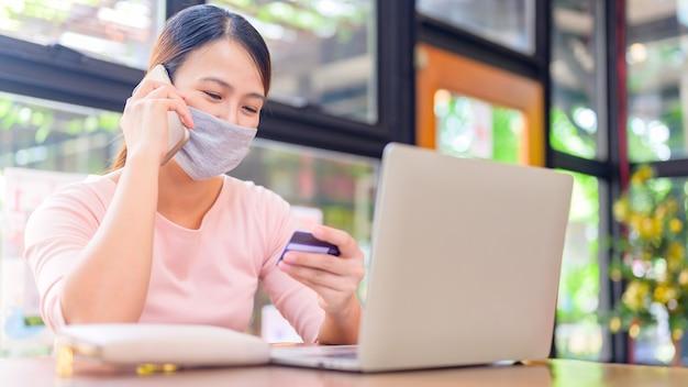 Mujer asiática con tarjeta de crédito para compras en línea y entrega a domicilio. nueva vida normal después del covid-19. quédate en casa y distanciamiento social.