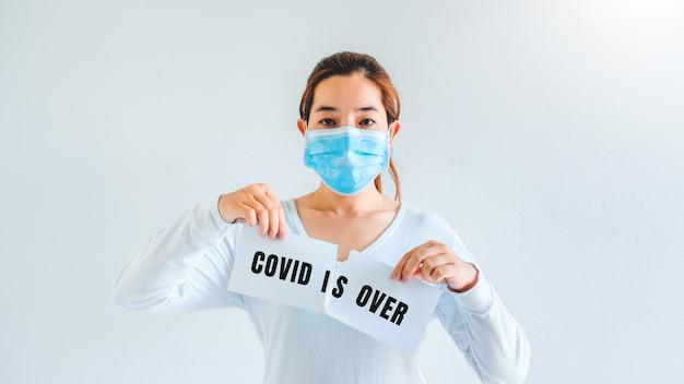 Mujer asiática con tarjeta de rasgado de máscara médica