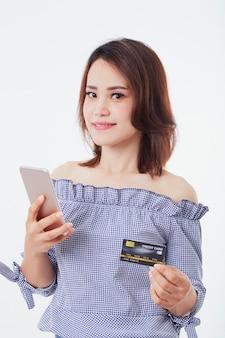 Mujer asiática con teléfono inteligente y crédito